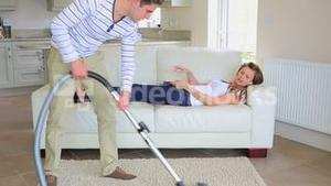 Woman relaxes on couch while man is hoovering