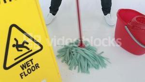 Woman cleaning near a caution sign