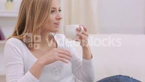 Calm woman thinking while drinking a hot drink