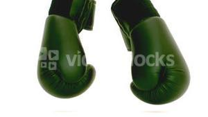 Green boxing gloves falling on the floor