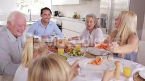 Mother serving carrots to son at family dinner