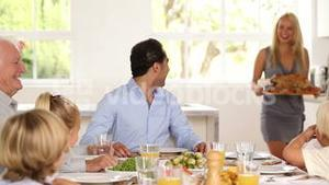 Family watching as mother brings turkey to table