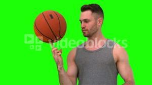 Man spinning the basketball on his finger on green background