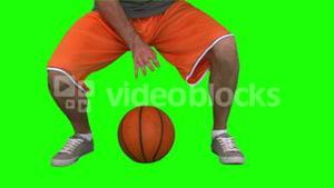 Man dribbling a basketball against green background
