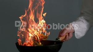 Peppers being tossed in a flaming wok