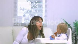 Mother saying boo to baby in highchair
