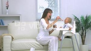Mother feeding her baby in living room