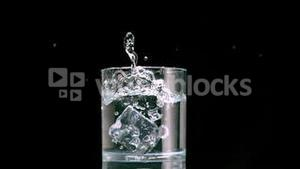 Ice cube falling in glass
