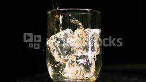 Whiskey being poured into a glass with ice cubes
