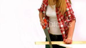 Blonde woman sawing a wood plank