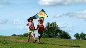 Little boy and little girl running with kite
