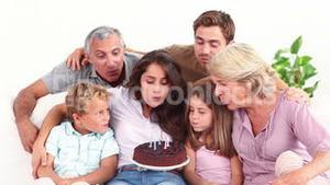 Family blowing candles on chocolate cake