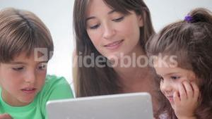 Mother and her children using tablet pc together