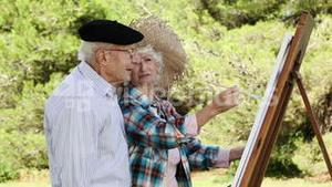 Old couple painting in the park