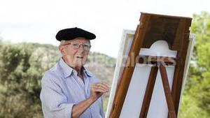 Old man painting in a park