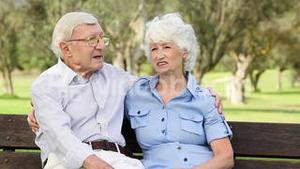 Old couple on a bench talking