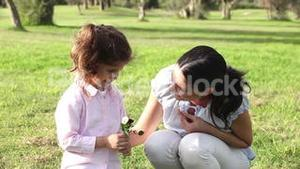 Little girl smelling a flower with mother