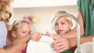 Parents washing dishes with their children