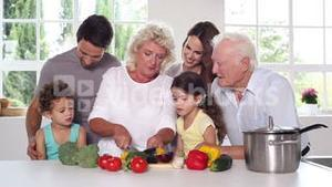 Granny cutting vegetables with the family around