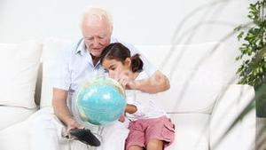 Grandfather and granddaughter looking at globe
