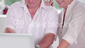 Old man learning to use laptop with partner