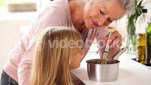Granny and little girl making chocolate sauce together