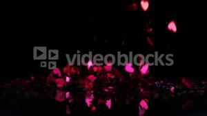 Pink heart confetti falling down on black background