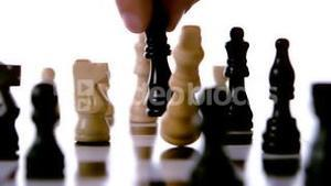 Black chess piece knocking over white