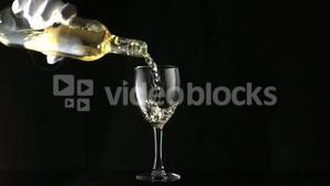 Gloved hand pouring white wine into glass