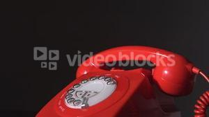 Red phone receiver dropping on dial phone on black background