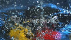 Three peppers falling into water