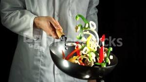 Chef tossing vegetable stir fry in wok