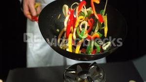 Chef tossing mixed vegetables in wok