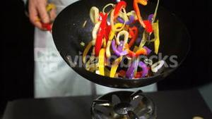 Chef tossing mixed vegetables in a wok