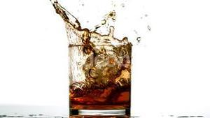 Ice cube falling in whiskey tumbler on white background