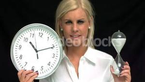 Blonde showing an hourglass and clock