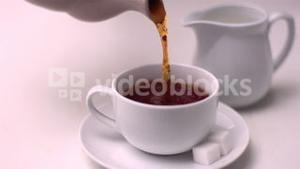 Tea pouring into tea cup