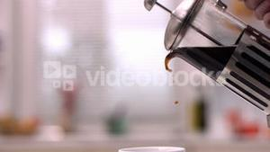 Cafetiere pouring coffee into cup