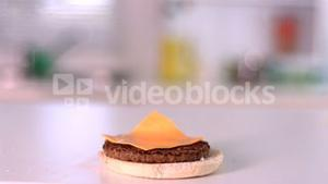 Cheese falling on bun burger in kitchen