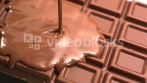 Melted chocolate being poured over a bar of chocolate