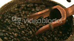 Coffee beans falling into basket with wooden scooper