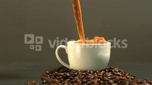 Coffee being poured into cup on mound of coffee beans