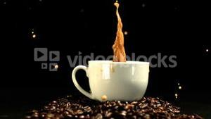 Sugar cube falling in coffee cup and splashing