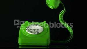 Receiver falling on green dial phone on black background