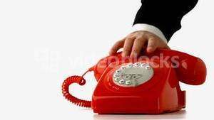Hand putting receiver down on red dial phone