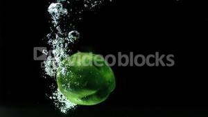Green pepper falling into water and floating
