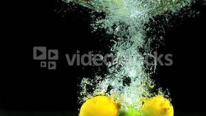 Lemons and limes dropping into water