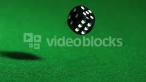 Black dice falling on green table close up