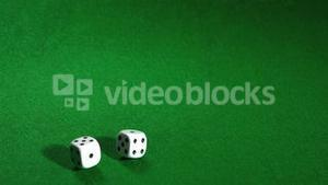 White dice rolling over green table