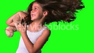 Little girl twirling and catching teddy on green screen